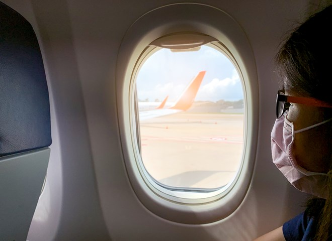 Women with facemask on plane